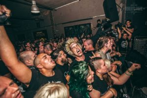 Crowd of punk in the mosh in front of the stage during a concert at the vintage industrial bar in zagreb