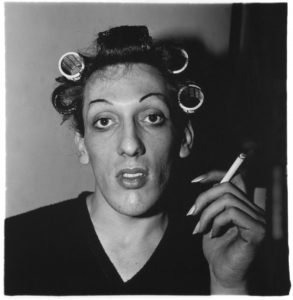 Diane Arbus A young man in curlers at home smoking a cigarettes